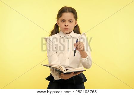 Girl Cute Serious Face Yellow Background. Child Girl School Uniform Clothes Holds Book And Pen. Chec