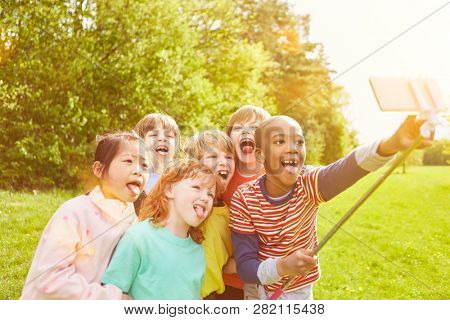 Group of kids in the park is making selfie with smartphone on selfie stick