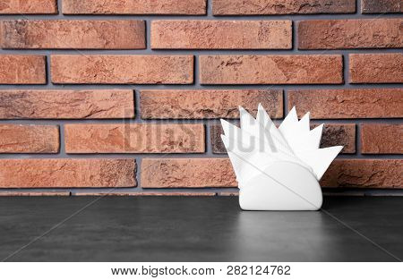 Napkin Holder With Paper Serviettes On Table Against Brick Wall. Space For Text