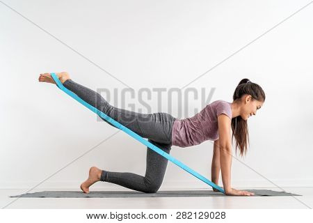 Resistance band fitness girl doing leg workout donkey kick floor exercises with rubber strap elastic. Glute muscle activation with kickback for cellulite.