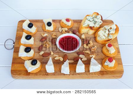 Camembert Cheese, Olives, Crackers, Nuts, Jam, Cranberries And Blue Cheese Slice On Toaster Bread An