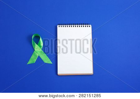 Light green ribbon and open notebook on blue background. Liver Cancer Lymphoma Awareness. Mental health awareness. Healthcare and medicine concept. poster