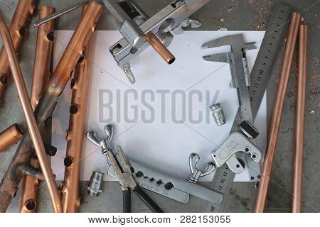 Brass pipes, pipe rammer, pipe cutter tool, calipers, pliers and a blank layout drafts on a fitter workbench. poster