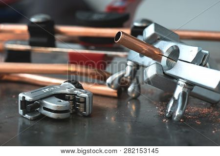 Pipe rammer tool and other pipework tools on a fitter workbench background. poster