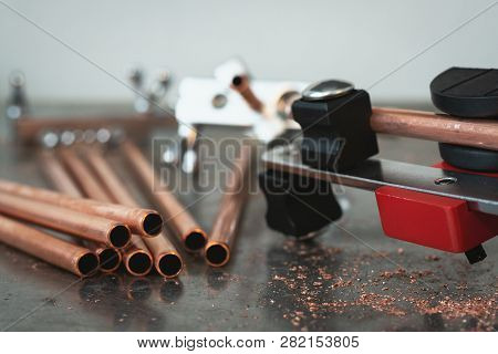 Pipe Bender Tool, Pipe Rammer And A Brass Pipes On A Workbench Of Fitter Background.
