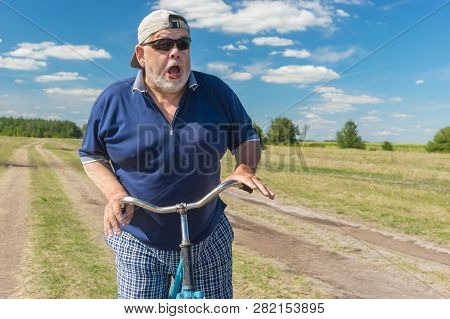 Funny Senior Shows His Fear To Ride On A Bicycle On A Country Road