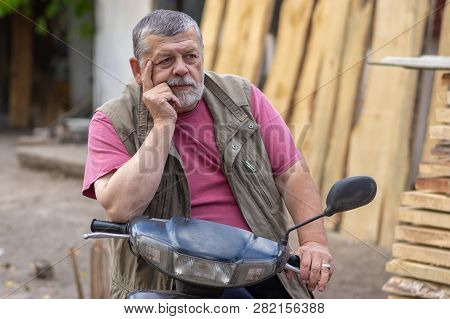 Nice Outdoor Portrait Of Bearded Senior Man Sitting On A Scooter And Being In Melancholy