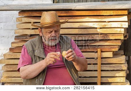 Bearded Senior Getting Ready To Drink Two Raw Hens Egg While Sitting Outdoor Against Pile Of Boards