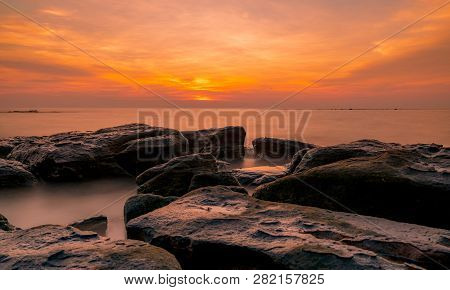 Rocks On Stone Beach At Sunset. Beautiful Beach Sunset Sky. Twilight Sea And Sky. Tropical Sea At Du