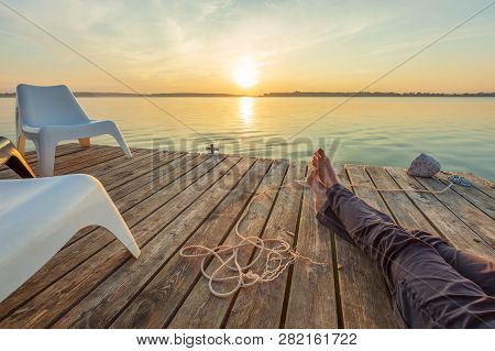 Man Relaxing On Footbridge With Naked Foot. Concept Of Waiting For Summer.