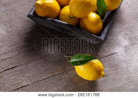Fresh Juicy Yellow Lemons With Leaves On Wooden Table.