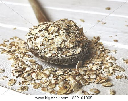 Oatmeal Or Coarse Oats On Wooden Spoon On Rustic Table With Vintage Filter