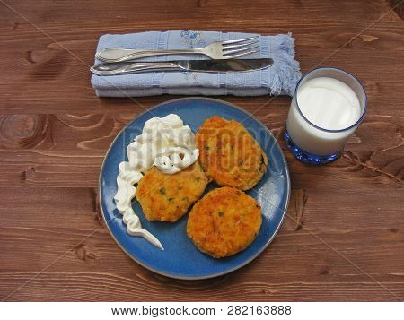 Rissoles Of Ham, Cheese  And Potatoes On Blue Plate, Milk In Glass And Sour Cream In Wooden Bowl On