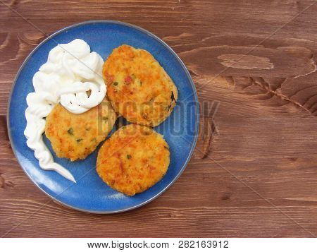 Rissoles Of Ham, Cheese  And Potatoes With Sour Cream On Blue Plate On Rustic Wooden Background