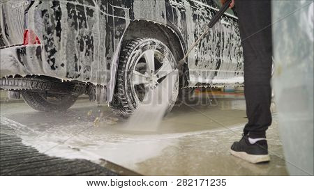 Man Worker Washing Cars Alloy Wheels On A Car Wash. Car Wash Wash The Car At The Car Wash.