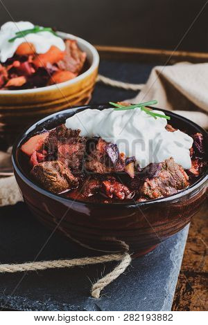 Two Bowls Of Borscht Soup With Hearty, Meaty Chunks Of Beef, Root Vegetables, Cabbage And Beets. Ser