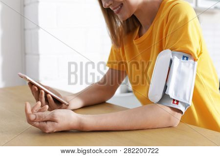 Woman Checking Blood Pressure With Modern Monitor And Smartphone At Table Indoors, Closeup. Cardiolo