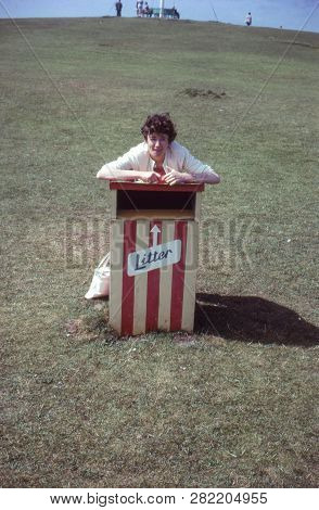 Vintage Photo Circa 1963 Of A Young Woman Leaning On A Holiday Resort Litter Bin In Cornwall, Uk. Se