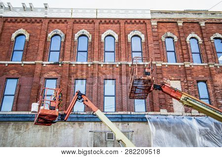 Crane On Construction Site. Two Cranes Work On Renovating And Restoring A Downtown Brick Building.