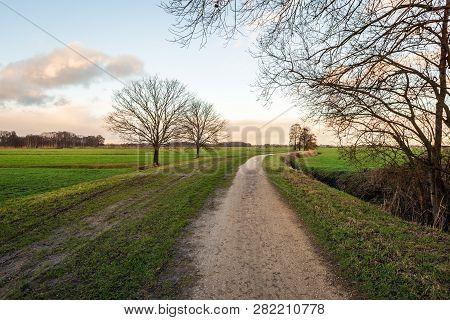 Curved Sand Path In A Dutch Polder Landscape In The Winter Season. The Photo Was Taken In The Binnen