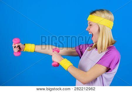 Fitness Concept. Girl Exercising With Dumbbell. Fitness Instructor Hold Little Dumbbell Blue Backgro