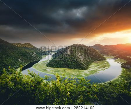 Top view of Rijeka Crnojevica flowing through mountains. Location place National park Skadar Lake, Montenegro, Balkans, Europe. Scenic image of popular travel destination. Explore the beauty of earth.