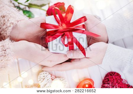 Valentine Gift. Young Couple Hands holding gift box with red bow gift over wooden background. St. Valentine's Day, Love concept. Top view, tabletop. Hands in Hands, romance, dating concept