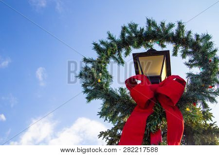 Christmas Lamppost Wreath. Vintage Lamppost With A Christmas Wreath And Red Bow. Horizontal Orientat