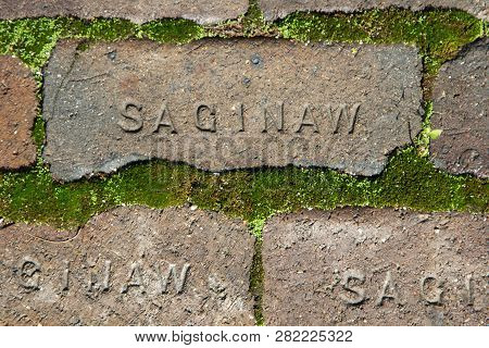 Saginaw Michigan. Rough Weathered Brick With Moss And The Word Saginaw Stamped In The Brick.