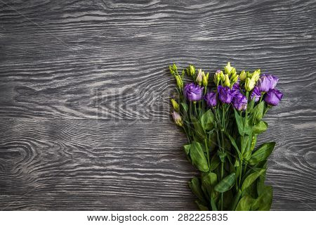 Beautiful Bouquet From Purple Eustoma Flowers On Dark Wooden Background. Copy Space, Top View