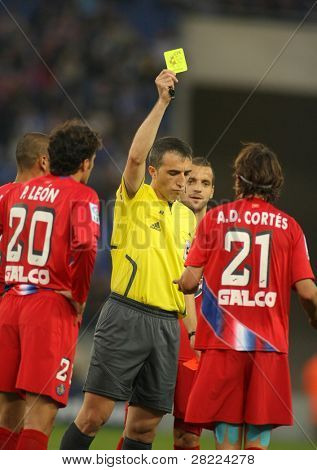 BARCELONA - NOV. 22: Referee Fernandez Borbalan (C) delivers yellow card to Cortes (R) of Getafe in a Spanish League match against RCD Espanyol at Estadi Cornella November 22, 2009 in Barcelona.