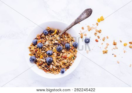 Bowl Of Homemade Granola With Fresh Berries On White Marble Table. Muesli Breakfast. Healthy Food Sw