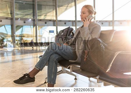 Female Traveler Talking On Her Cell Phone While Waiting To Board A Plane At Departure Gates At Airpo
