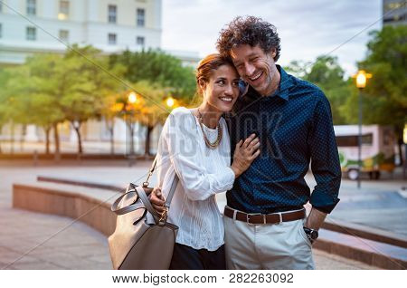 Romantic mature couple enjoying evening walk after office. Cheerful man and beautiful woman embracing while walking on city streets. Handsome man and woman spending evening together outdoors.