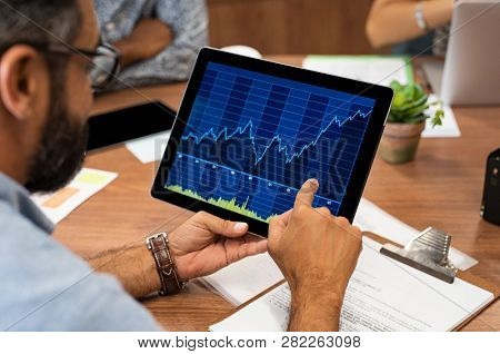 Mature latin businessman reading business graphs and stock charts on digital tablet. Rear view of business man holding tablet computer with stock analytics and abstract graphs. Close up hands working.