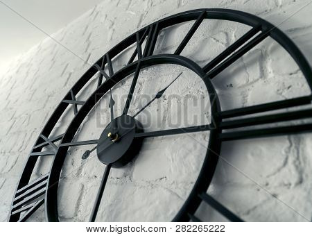 Vintage Clock With Roman Numeral. Wall Clock-face Dialrustical On White Brick Wall In The Apartment,