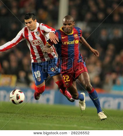 BARCELONA - FEB 5: Reyes(L) of Atletico fight with Abidal(R) of Barcelona during the match between FC Barcelona and Atletico Madrid at the Nou Camp Stadium on February 5, 2011 in Barcelona, Spain