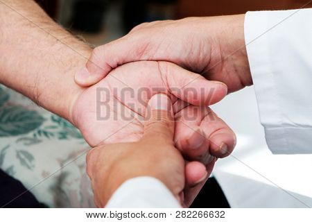 closeup of a caucasian man, in a white coat, moving the hand of a senior caucasian patient man, at his home or at a nursing home poster