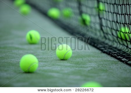 Tennis or paddle balls on synthetic grass of paddle court with net on the background poster
