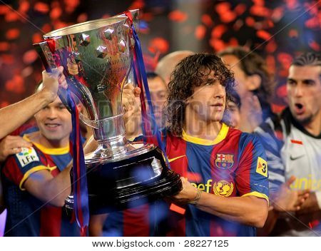 BARCELONA - MAY 15: Carles Puyol of FC Barcelona holds the La Liga trophy after the match between Barcelona and Deportivo La Coruna at Camp Nou Stadium on May 15, 2011 in Barcelona, Spain