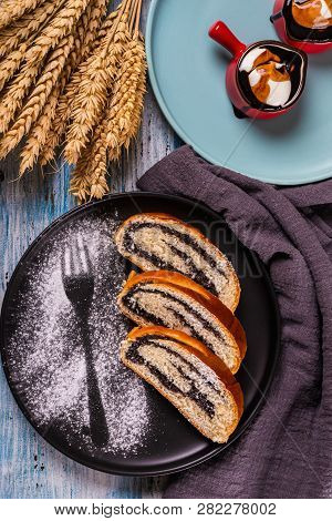 Poppy Seed Strudel On Dark Plate With Silhouette Of Fork Made By Sugar