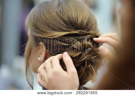 Young Woman/bride Getting Her Hair Done Before Wedding Or Party. Wedding Or Prom Ball Hairstyles.
