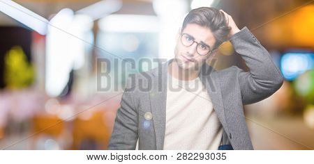 Young business man wearing glasses over isolated background confuse and wonder about question. Uncertain with doubt, thinking with hand on head. Pensive concept.