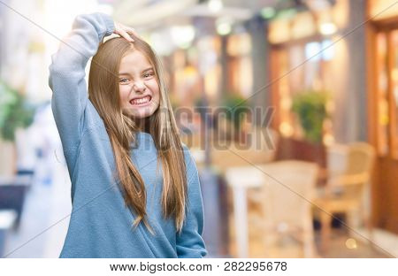 Young beautiful girl wearing winter sweater over isolated background confuse and wonder about question. Uncertain with doubt, thinking with hand on head. Pensive concept.