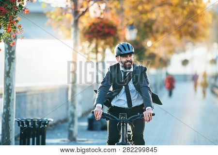 Hipster Businessman Commuter With Electric Bicycle Traveling Home From Work In City.