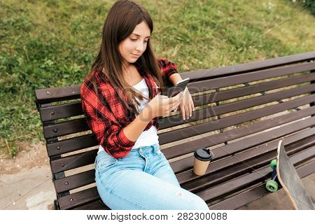 Girl Teenager 11-12 Years Old Sits On Bench Near Skate In Park In Summer On. In The Hands Of The Sma