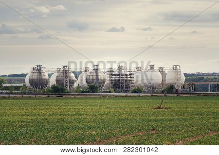 Liquid And Fluid Gas Holder Storage, Sphere Shape Container Tanks, Green Field In Foreground