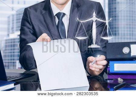 A Closeup Of A Businessman At A Table Showing A Contract To Sign With Scales Hanging At The Foregrou