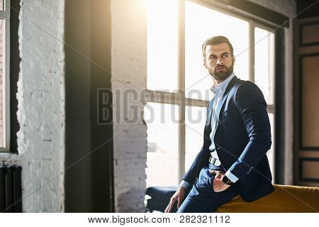 Fashion Portrait. Young Bearded Successful Businessman In Stylish Suit Is Standing At Office And Thi