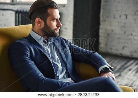 Generating Ideas...young And Charming Businessman Is Thinking About Business While Sitting On The So
